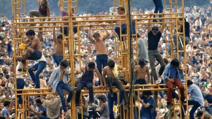 Bethel, New York: August 1969. Crowd and people sitting on the sound tower. ©Elliot Landy/The Image Works.